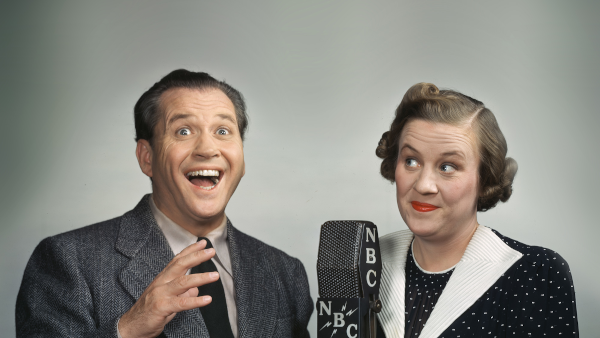 Photo of Jim and Marian Jordan performing Fibber McGee and Molly on an NBC radio microphone