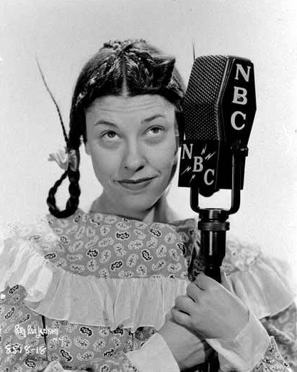 Judy Canova posing in pigtails with an NBC Radio microphone