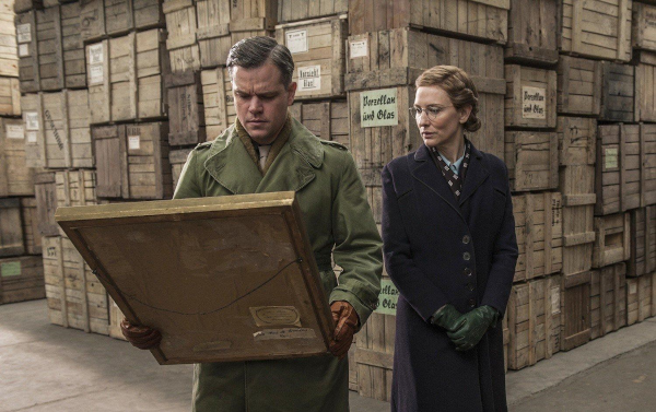 Matt Damon examing a painting in a warehouse as Cate Blanchett observes in the 2014 movie Monuments Men