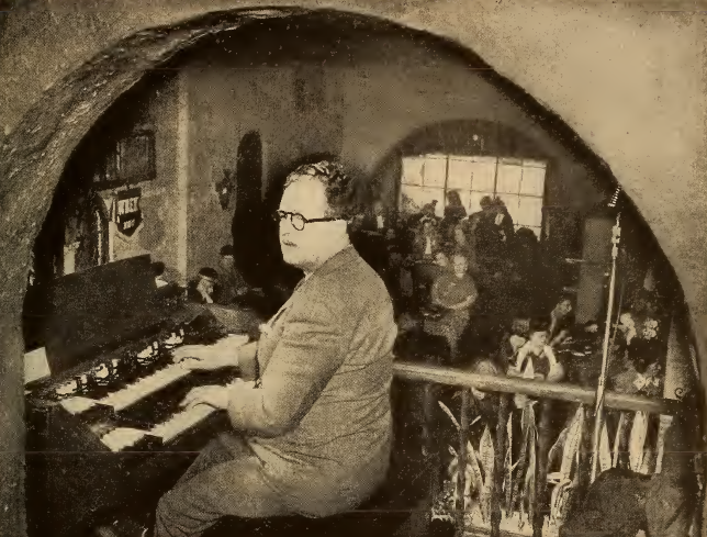 Photo of Nelson Selby playing an organ on the balcony of Laube's Old Spain restaurant in Buffalo, New York, in the 1940s