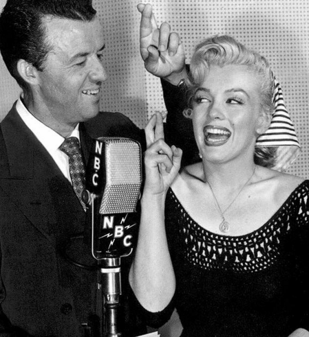 Wendell Niles and Marilyn Monroe with fingers crossed at an NBC Radio microphone in 1952